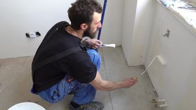 Wall paint worker. Young caucasian brown haired man with beard and black t-shirt blue dungarees working trousers is crouching down painting with mini fabric stock footage