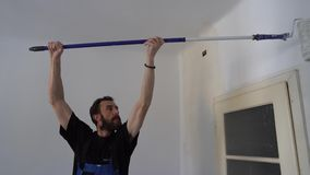 Wall paint worker. Young caucasian brown haired man with beard and black t-shirt blue dungarees working trousers is painting with paint stick roller extension stock video footage