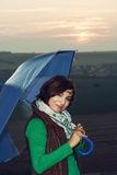 Young caucasian brunette with blue umbrella and sunset backgroun Stock Photos