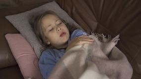 Young caucasian brunette girl in blue sweater laying under the warm blanket and coughing. Little child having fever and. Staying at home stock footage