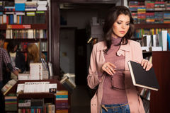 Young caucasian brunette girl in a bookstore Stock Photos