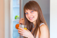 Young caucasian brunette girl with a glass of juice in the kitch Stock Photo