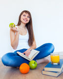 Young caucasian brunette girl with a glass of juice in the kitch Stock Photos