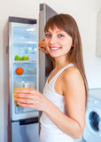 Young caucasian brunette girl with a glass of juice in the kitch Stock Images