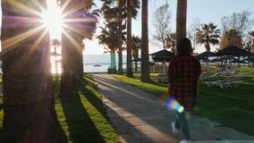 Young caucasian brunette girl in red plaid shirt walking on promenade surrounded by palm trees. Attractive woman walks to quay thr. Ough hotel beach area. Young stock video