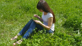 Young caucasian brunette girl sitting on grass on the meadow in the park and using digital tablet pc. Happy woman stock footage