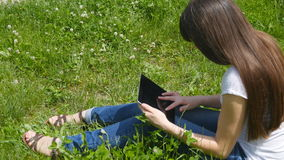Young caucasian brunette girl sitting on grass on the meadow in the park and using digital tablet pc. Happy woman stock video