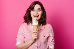 Young Caucasian brunette girl with wavy hair on pink background. Stylish young woman with ice cream isolated over pink studio. Background. Lady wearing royalty free stock images