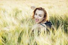 Young caucasian brunette is hidden in the wheat field. Young positive caucasian brunette is hidden in the wheat field. Beauty and nature Stock Images