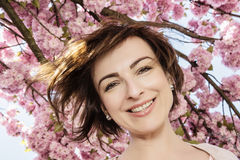 Young caucasian brunette posing with flowering sakura tree Royalty Free Stock Photos