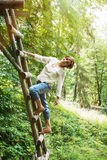 Young caucasian brunette posing on the wooden ladder Royalty Free Stock Image