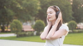 Young Caucasian Brunette Woman with Headphones Outdoors stock video