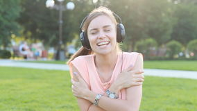 Young Caucasian Brunette Woman with Headphones Outdoors stock footage