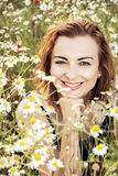 Young caucasian brunette woman posing in daisy meadow, beauty an Stock Photo