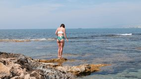 Young caucasian brunette woman in swimsuit with cellulite on her legs walking along the shore of rocky beach.  stock footage