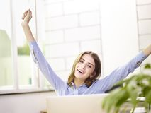 Young caucasian business executive celebrating completion of task. Young caucasian business executive stretching arms in office celebrating completion of task stock photo