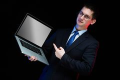 Portrait of confident handsome stylish businessman holding laptop in his hands on black background. Young caucasian business man in black suit in glasses Stock Photo