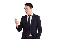 Young Caucasian business man looking at mobile phone smiling Royalty Free Stock Photography