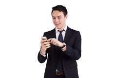 Young Caucasian business man looking at mobile phone smiling Royalty Free Stock Photos