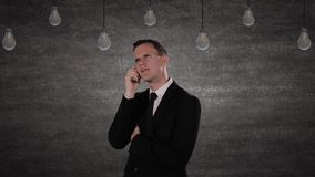 Business person getting bright idea. Young Caucasian business person getting bright idea under glowing light bulb while wearing formal suit stock footage