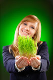 Young Caucasian business woman studio shot on green background. Holding fresh green grass. Focus on grass. Royalty Free Stock Image
