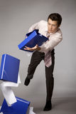 Young caucasian businessman droping a stack of binders - failure Stock Image