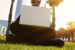 Young caucasian businessman in formal clothes working at sunny day on green grass on laptop.Closeup. Blurred background. Royalty Free Stock Images
