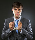 Young caucasian businessman with handcuffed hands. Studio shot. Gray background Stock Photos