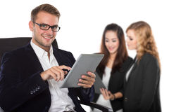 Young caucasian businessman holding a tablet pc, his staff on th royalty free stock images