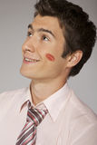 Young caucasian businessman with lipstick kiss mark on his cheek Stock Photos