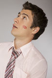 Young caucasian businessman with lipstick kiss mark on his cheek Royalty Free Stock Images