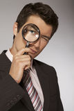 Young caucasian businessman with magnifying glass Stock Image