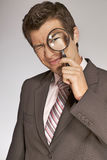 Young caucasian businessman with magnifying glass Stock Photos