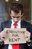 Young caucasian businessman at office exterior with executive for rent note Stock Photo