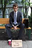 Young caucasian businessman in park with executive for rent sign Royalty Free Stock Photos