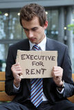 Young caucasian businessman in park with executive for rent sign Royalty Free Stock Photography