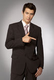 Young caucasian businessman pointing his finger right Royalty Free Stock Photos
