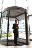 Young caucasian businessman at revolving door Stock Images