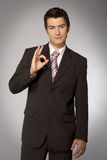 Young caucasian businessman showing ok gesture Stock Images