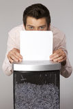 Young caucasian businessman shredding documents Royalty Free Stock Image