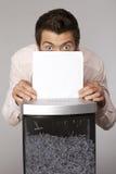 Young caucasian businessman shredding documents Royalty Free Stock Photos