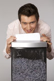 Young caucasian businessman shredding documents Stock Photos