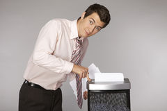 Young caucasian businessman shredding documents Royalty Free Stock Photo