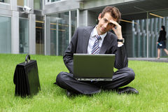 Young caucasian businessman sitting on grass Royalty Free Stock Photo