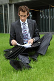 Young caucasian businessman sitting on grass with documents Stock Images