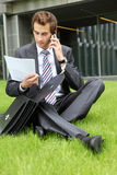 Young caucasian businessman sitting on grass with documents Stock Photos