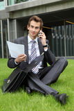 Young caucasian businessman sitting on grass with documents Stock Photo