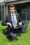 Young caucasian businessman sitting on grass with documents Royalty Free Stock Photo