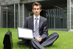 young caucasian businessman sitting on grass using his laptop Stock Images