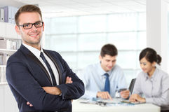 Young Caucasian businessman standing with his colleague behind stock photo